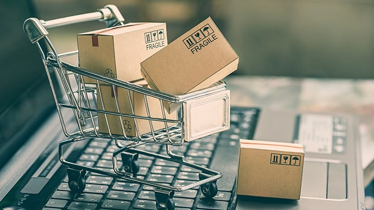 shopping cart with boxes on laptop